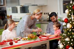 Mother serving turkey to his family in Christmas dinner Royalty Free Stock Photos