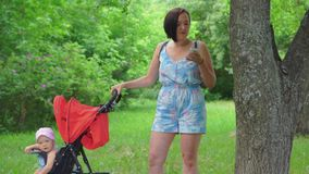 A mother shakes a child in a stroller and nervously writes a message in her mobile phone. In nature, a mother shakes a child in a stroller and nervously writes a stock video footage