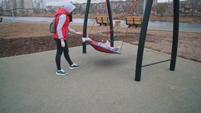 Mother shakes her child on swing in park on cloudy day. stock footage