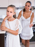 Mother shaming daughter for misbehaviour in domestic interior. Upset mother shaming daughter for misbehaviour in domestic interior. focus on daughter Royalty Free Stock Images