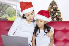 Mother shopping online with her daughter. Christmas holiday concept. Young women shopping online with her daughter while sitting on the couch Stock Images