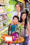 Mother shopping at the supermarket Stock Photo