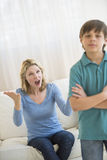 Mother Shouting While Son Ignoring Her At Home. Angry mother shouting while son ignoring her at home Stock Image