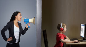 Mother shouts at his son. Tween son in headphones looks at a computer screen while his mother shouts at him through a megaphone Royalty Free Stock Photo