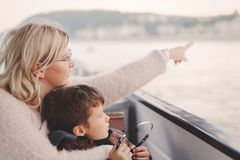 Mother showing away to son by headphones on cruise tour Stock Photo