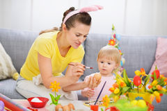 Mother showing baby how to paint on Easter egg Royalty Free Stock Images