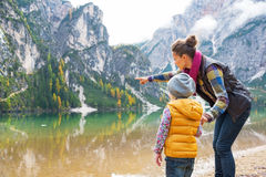 Mother showing baby something while on lake braies Stock Photos