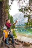 Mother showing baby something while on lake braies Stock Photo