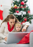 Mother showing baby something in laptop. Near Christmas tree stock photos