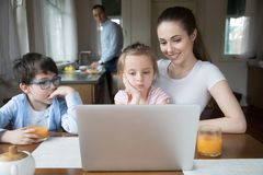 Mother showing cartoon on computer for children while father cooking stock photography