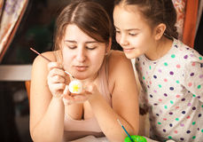 Mother showing daughter how to paint eggs Royalty Free Stock Photo