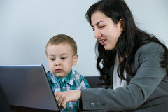 Mother showing her baby boy something on the computer screen. Mother with her toddler son at the computer Stock Photography