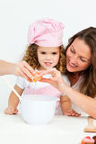 Mother showing her daughter how to break eggs Stock Images