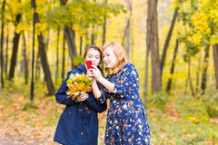 Mother showing her Teenage girl photos on mobile phone outdoor in autumn nature Stock Images