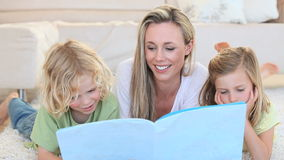 Mother showing an image in a book to her children Stock Photography
