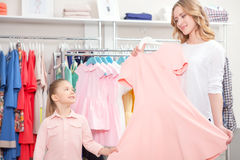 Mother showing a pastel pink dress to her small Stock Images