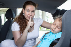 Mother showing shh gesture when child asleep. In car Royalty Free Stock Photography