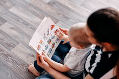 Mother and baby learning teaching book. Mother is showing some pictures in a book to her son royalty free stock image