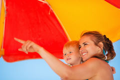 Mother showing something baby on beach. Happy young mother showing something baby on beach Stock Photography