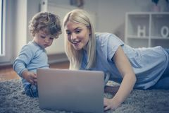 Mother showing something interesting her son on laptop. Childhood Stock Photo