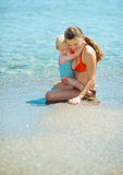Mother showing something to baby girl on sea coast Stock Image