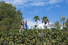Mother showing something to her son. Adult women in sunglasses pointing on something with finger to show her son. Green bushes on foreground Stock Photo