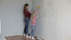 A mother showing to a daughter how to wallpaper. A young pregnant mother showing to a small blond daughter how to wallpaper stock video