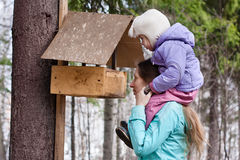 Mother shows her daughter the bird feeder Stock Photography