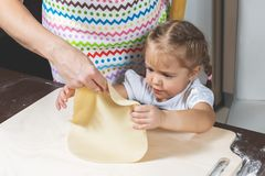 Mother shows little daughter how to cook the dough for making cookies.  stock photography
