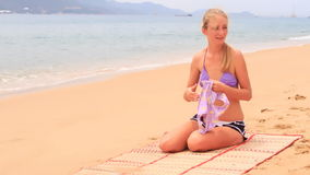 Mother shows swimsuit to daughter sitting on sandy beach stock video footage
