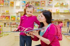 Mother shows to daughter big fold-out book Royalty Free Stock Image