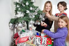 Mother And Siblings Decorating Christmas Tree Stock Photography
