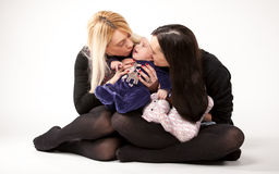 Mother and sister kissing lithe baby on floor Stock Image