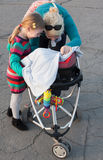 Mother and sister playing peek a boo with his baby brother sitting in a stroller Stock Images
