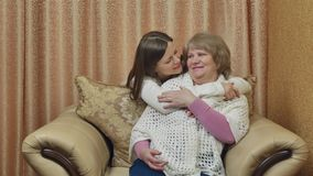 Mother sits in a chair, and her daughter hugs. Two women talk and smile. Two beautiful girls-mother and daughter hugging. Expressing tender feelings and stock video