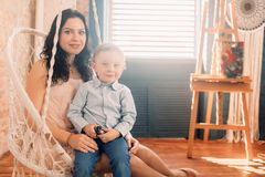 Mother sits with her little son in a chair stock photo