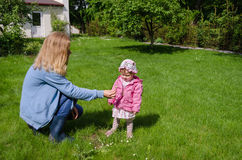 Mother sits in meadow daughter gather daisies Stock Image