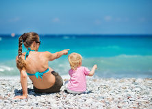 Mother sitting with baby on sea. Rear view Stock Photos