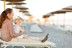 Mother sitting with baby on sunbed on the beach. Young mother sitting with baby on sunbed on the beach at evening and looking into the distance Royalty Free Stock Photography