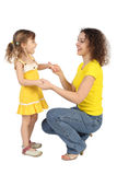 Mother sitting behind daughter and holding hands Stock Images