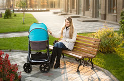 Mother sitting on bench at park and swaying baby stroller Royalty Free Stock Photos