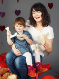 Mother sitting on chair with baby girl toddler on her laps knees in studio holding wooden letters love smiling laughing Royalty Free Stock Photography