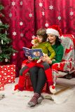 Mother reading Christmas book to her kid stock photo