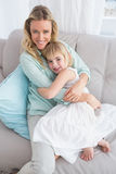Mother sitting on the couch with her daughter smiling at camera Royalty Free Stock Photos