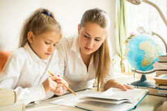 Mother sitting with daughter at desk and explaining task at home Stock Images