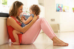 Mother Sitting With Daughter At Home stock images