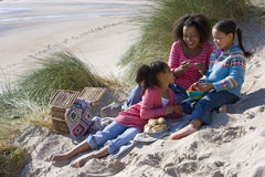 Mother sitting with daughters on beach Stock Image