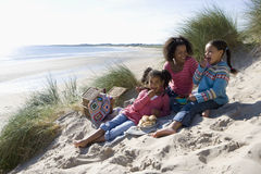 Mother sitting with daughters on beach Stock Photos