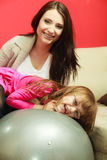 Mother sitting on exercise ball with daughter Stock Images