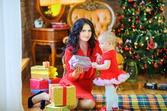Mother sitting on the floor near the Christmas tree gives a gift to her beloved daughter royalty free stock image